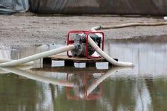 Bensinvattenpump med f?rbindelsevita brandslangar f?r stor diameter som l?mnas p? tr?paletten att pumpa flodvatten i v?g fr?n fam royaltyfria foton