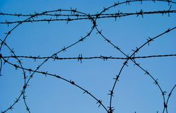 Bent barbed wire in a military area. Metal barbed wire of an enclosure military zone royalty free stock image