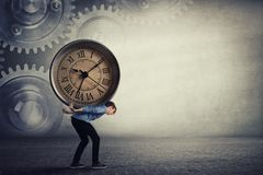 Free Bent Down Guy Carrying A Big Heavy Clock On His Back. Overloaded Student Tired Of Daily Tasks, And Difficult Burden. Time Pressure Stock Photos - 165587193