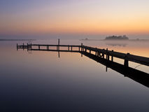 Bent jetty with mooring post. During spectacular sunset over lake Stock Image