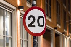 20mph Sign UK at night. Bent 20mph sign on a street at night stock photos
