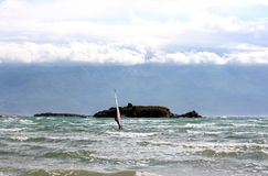 Bent Windsurfer on a sea near island Royalty Free Stock Photos