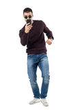 Bent young casual man taking photo with cell phone aiming at camera. Full body length portrait isolated over white studio background royalty free stock images