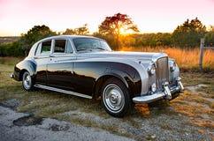Bentley 1960 brille avec le lustre au coucher du soleil sur une route de campagne de colline du Texas Photos stock