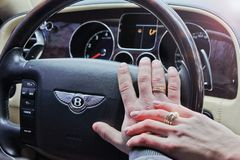September 18, 2012, Kyiv. Ukraine. Bentley Continental Flying Spur. Bentley Continental Flying Spur. Hands of man and woman together on the steering wheel. In royalty free stock photos