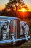 Verticle close up front view of vintage luxery limousine with sunset behind. 1962 Bentley front view in the fading light of sunset with chrome fender Stock Image