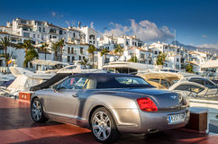 Bentley parked in Puerto Banus next to yachts mooring Royalty Free Stock Image