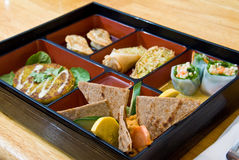 A bento box. Including samples of Sandy Spring Rolls, Basil Rolls, Pot Stickers, Spaghetti Squash Cake and Red Pepper Hummus stock photos