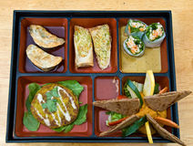 A bento box. Including samples of Sandy Spring Rolls, Basil Rolls, Pot Stickers, Spaghetti Squash Cake and Red Pepper Hummus royalty free stock photography