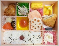 Bento box. Bento is Japanese traditional takeaway lunch box divided into small section with various food and Japanese sweet i royalty free stock photo