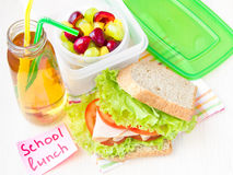 Bento lunch for your child in school, box with a healthy sandwich and fruit salad and apple juice in the bottle stock photography