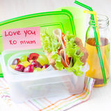 Bento lunch for your child in school, box with a healthy sandwich and fruit salad and apple juice in the bottle royalty free stock images