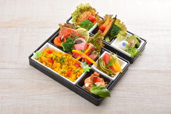 Bento meal of rice, salmon, broccoli, lettuce and noodle on wood Royalty Free Stock Images