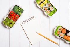 Bento pudełko z różnym jedzeniem, świeżymi veggies i owoc, Noteboo zdjęcie royalty free