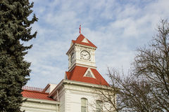 Benton County Courthouse, Corvallis, Oregon. The clock tower of Benton County Courthouse against a blue and white cloud-mottled sky. Trees frame the tower Royalty Free Stock Image