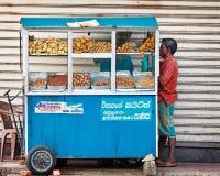 BENTOTA SRI LANKA, APR, - 27: Mężczyzna kupuje jedzenie w małym przenośnym str Zdjęcia Stock