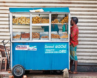 BENTOTA, SRI LANKA - APR 27: Man buys food in small portable str Stock Photos