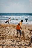 BENTOTA, SRI LANKA - 28 APRIL: De tieners spelen veenmol met knuppel en Stock Afbeelding
