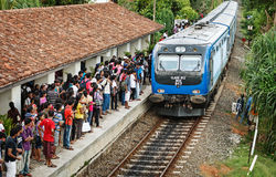 BENTOTA, SRI LANKA - 28 APRIL 2013: De trein komt aan post met w aan Royalty-vrije Stock Foto