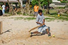 BENTOTA, SRI LANKA - 28 DE ABRIL: Grillo del juego de niños con el palo y Fotos de archivo