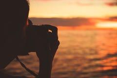 Benutzen Frauen Kamera, um geschossenes Meer und Sonnenuntergang zwischen Reise zu nehmen lizenzfreies stockfoto