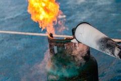 Benutzen Sie einen Feuerlöscher, um am Gasbehälter abzufeuern Stockfoto