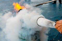 Benutzen Sie einen Feuerlöscher, um am Gasbehälter abzufeuern Lizenzfreie Stockfotografie
