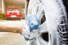 Benutzen Sie Ihre rechte Hand, um den Schwamm zu fangen und das Autofenster zu polieren Konzeptwaschanlage lizenzfreie stockfotografie