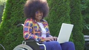 Benutzt lächelnde Afroamerikanerfrau des Porträts mit einer Afrofrisur, die in einem Rollstuhl behindert ist, einen Laptop, der b stock video footage