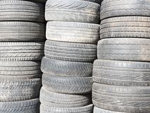 Benutzte, alte Reifen stapelten ein auf einem anderen nahe bei Gesch?ftsgarage stockbilder