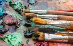 Benutzte Bürsten auf der Palette eines Künstlers der bunten Ölfarbe für Dr. Lizenzfreie Stockfotografie