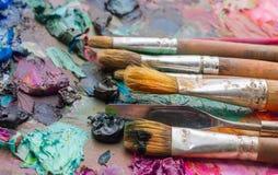 Benutzte Bürsten auf der Palette eines Künstlers der bunten Ölfarbe für Dr. Stockbild