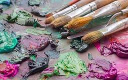 benutzte Bürsten in der Palette eines Künstlers der bunten Ölfarbe für Dr. Lizenzfreie Stockfotografie