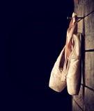 Benutzte Ballettschuhe, die am hölzernen Hintergrund hängen Lizenzfreie Stockbilder