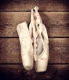 Benutzte Ballettschuhe, die am hölzernen Hintergrund hängen Lizenzfreie Stockfotografie