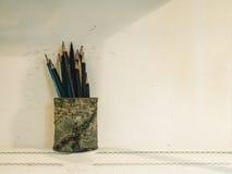 Benutzte Bleistifte im Bleistifthalter gegen Betonmauerhintergrund Lizenzfreie Stockfotos