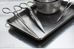 Benutzte chirurgische Instrumente auf einem rostfreien Behälter stockbild