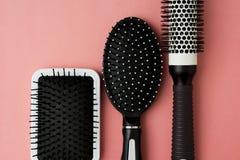 Benutzte Haarbürstenwerkzeuge auf rosa oder korallenrotem Hintergrund mit Kopienraum Schönheitsmode, Haarpflegehintergrund lizenzfreies stockbild