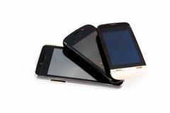 Benutzte Handys auf weißem Hintergrund Stockfotografie