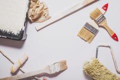 Benutzte malende Werkzeuge mit den roten Griffen bedeckt in der warmen weißen Farbe ausgebreitet in einer Zusammensetzung auf ein lizenzfreie stockfotografie