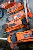 Benutzte orange hydraulische Wagenheber auf konkretem Boden Stockfoto