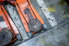 Benutzte orange hydraulische Wagenheber auf konkretem Boden Stockfotos