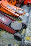Benutzte orange hydraulische Wagenheber auf konkretem Boden Lizenzfreies Stockbild