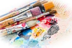 Benutzte Pinsel auf einer bunten Palette Stockfoto