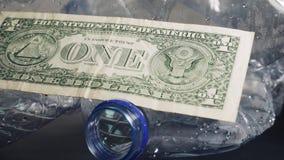 Benutzte Plastikflaschen und Geld bereiten Sie überschüssiges Konzept auf Globale Erwärmung und Verunreinigung stock footage
