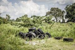 Benutzte Reifen gelassen auf einem Gebiet stockbild