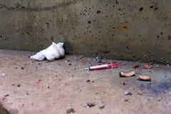 Benutzte Spritze unten geworfen mit Zigarettenkippen Konkreter Schmutzboden Stockfotografie