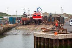 Benutzte und getragene Schleppnetzfischer des Brunnens auf dem Reparaturhelling im beschäftigten Fischereihafen von Kilkeel in de stockfotos