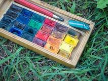 Benutzte wasserbasierte Farbfarbe in den Behältern auf dem grünen Hintergrundabschluß oben Stockfoto