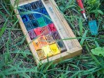 Benutzte wasserbasierte Farbfarbe in den Behältern auf dem grünen Hintergrundabschluß oben Lizenzfreies Stockfoto